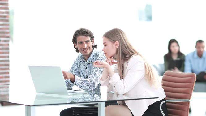 Man smiling at a woman in a meeting